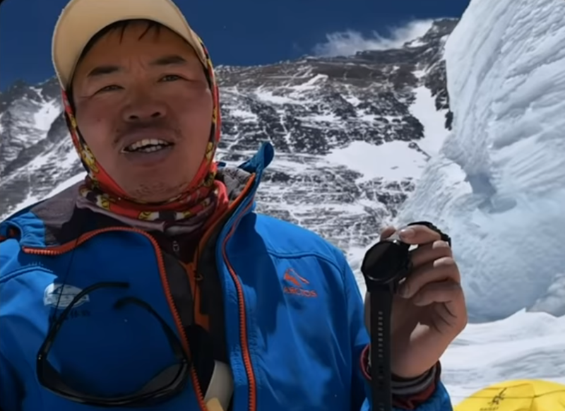 Mountain climber holding a smartwatch