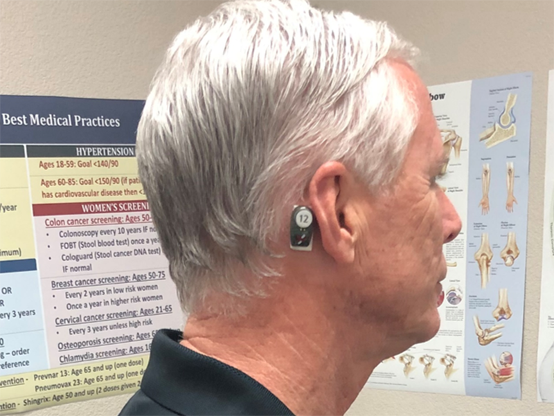 A man wearing a medical wearable device behind the ear