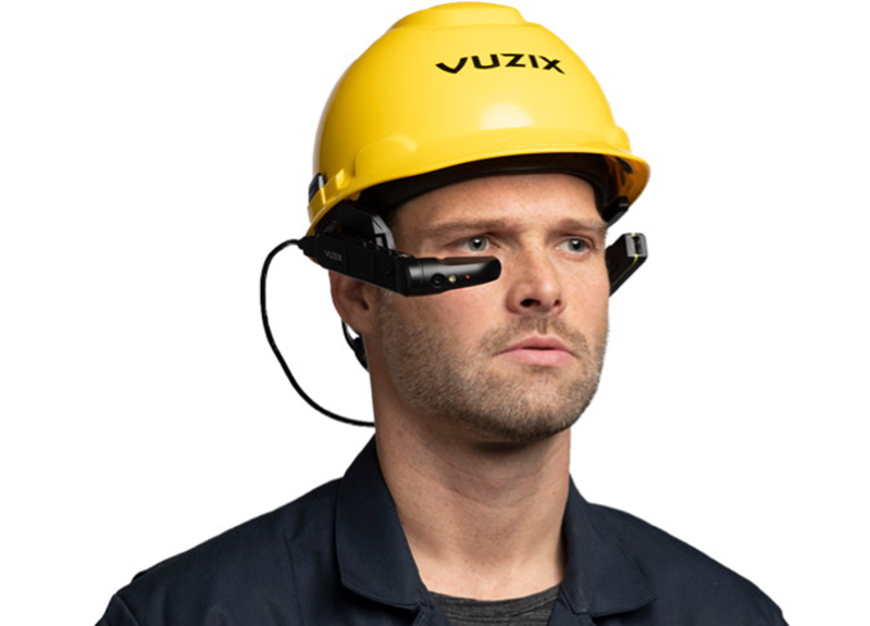 An industrial worker wearing a hat fitted with smartglasses.