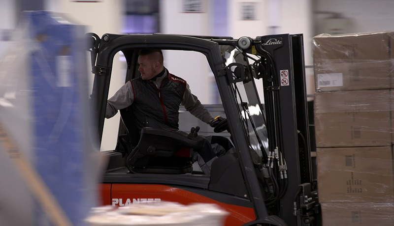 A factory worker operating forklift