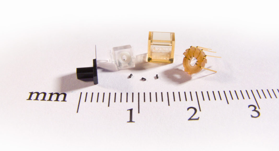 Examples pushing the limits with micro injection molding: From the left: (LCP) 76 µm thin-wall, (ABS & TPU) 2-shot with 2 mm soft diameter center ring, (PEI/Ultem) micro features with 250 µm diameter lenses, (PEEK) lead frame insert molding. In the center: (LCP-mineral filled) 800 µm longest feature.