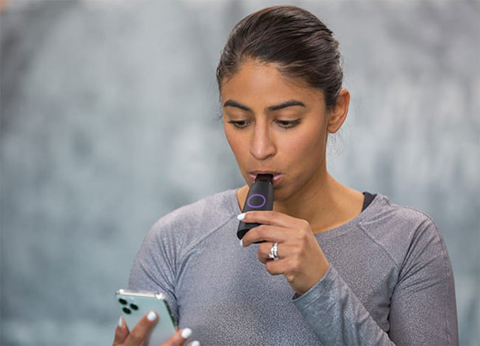A person blowing into a device